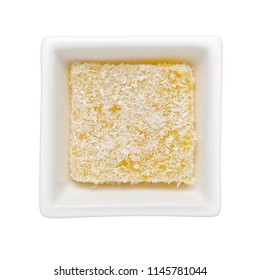Traditional Kueh Sago covered with coconut shreds in a square bowl isolated on white background;