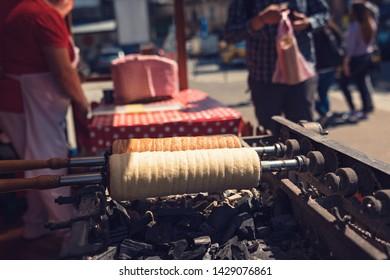 Traditional kurtoskalacs hungarian spiral pastry, sweet street food sugar kurtosh sweet kurtosh kalach baked on the wooden grill. Kurtos kalacs best kurtos cinnamon baked on the street with charcoal
