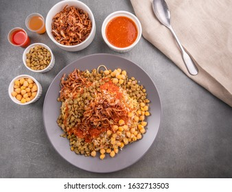 Traditional Kushary, consist of boiled lentil, rice, pasta, bulgur, chick peas, vermicelli and fried onions with spicy tomato sauce and vinegar sauce