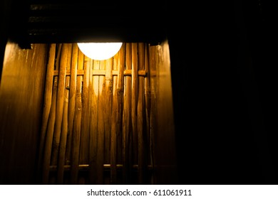 Traditional Lamp with Warm Light and Bamboo Wall for Background