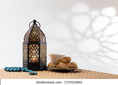 Traditional lantern, dates fruit, rosary beads and a cup of Arabic coffee on a  small straw mat with arabesque shadow effect.