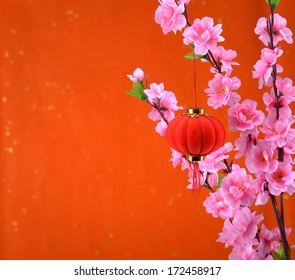 Traditional lantern and peach blossom on a festive background.