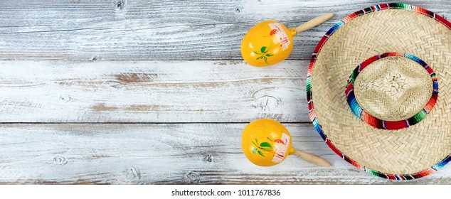 Traditional large sombrero with maracas for Cinco de Mayo holiday celebration on weathered white wooden boards