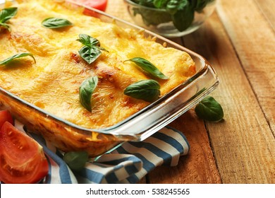 Traditional lasagna in glass baking dish and tomatoes on wooden table