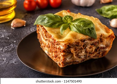 Traditional lasagna made with minced beef bolognese sauce and bechamel sauce topped with basil leaves.