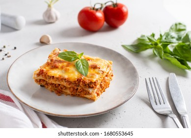 Traditional lasagna made with minced beef bolognese sauce and bechamel sauce topped with basil leaves on light background. Recipe, restaurant menu. Side view, close up