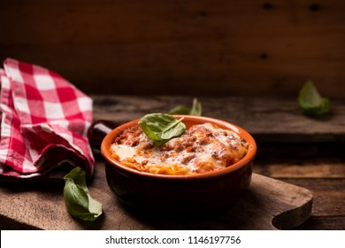 Traditional lasagne in a casserole dish on wooden table