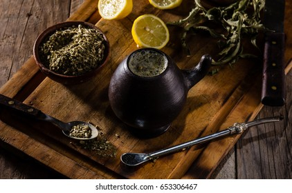 Traditional Latin American hot herb drink. Yerba mate, herb mate in clay mug. Chilean argentine mate on wooden background