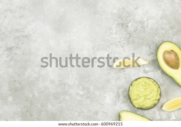 Traditional Latin American sauce guacamole in a bowl and ripe avocados and lemons. Top view, copy space. Food background. Toning