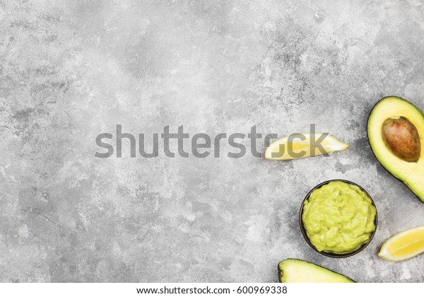 Traditional Latin American sauce guacamole in a bowl and ripe avocados and lemons. Top view, copy space. Food background.