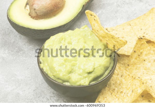 Traditional Latin American sauce guacamole in a bowl and nachos. Toning.