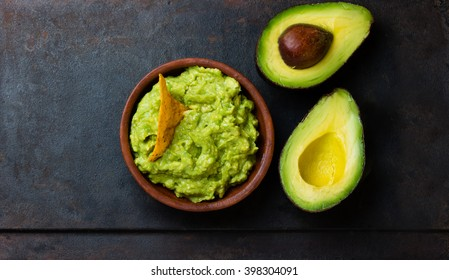 Traditional latinamerican mexican sauce guacamole in clay bowl and cut half avocado on dark background. Top view