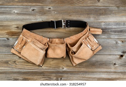 Traditional leather tool belt on rustic wooden floor.
