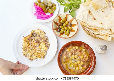 Traditional Lebanese Breakfast - with fava beans, bread, olives, pickles and eggs with awarma
