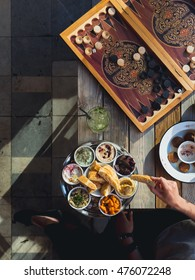 Traditional Lebanese cafe in Beirut: table with backgammon and meze plate and falafel , female hand with pita, view from above, vertical