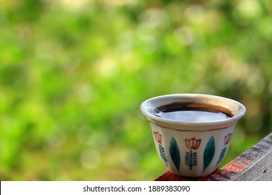 A traditional Lebanese coffee cup against a green background. - Shutterstock ID 1889383090