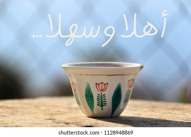 A traditional Lebanese coffee cup on a wooden table. Translation: traditional Lebanese greeting to make guests welcome.