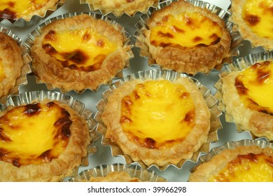 Traditional Lisbon egg tarts - pastries pasteis de nata in tin moulds