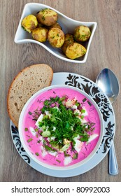 traditional lithuanian cold borscht with beet, eggs and greens, served with hot young potatoes with bread