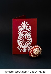 Traditional lithuanian Easter egg,  lithuanian is called marguciai,  painted with beeswax and postcard with handmade papercut, where are representing  an egg, sun, birds, flowers -  symbols of spring