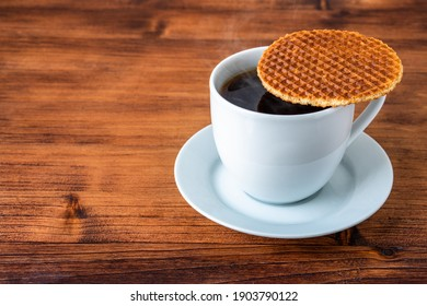 Traditional local authentic Dutch Netherlands sweet fresh homemade tasty stack brown golden waffle melt salted caramel honey syrup for dessert in cafe with hot warm coffee milk tea call Stroopwafel