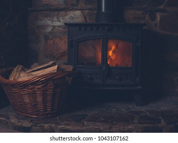 A traditional log burner with a basket of firewood and a lit fire