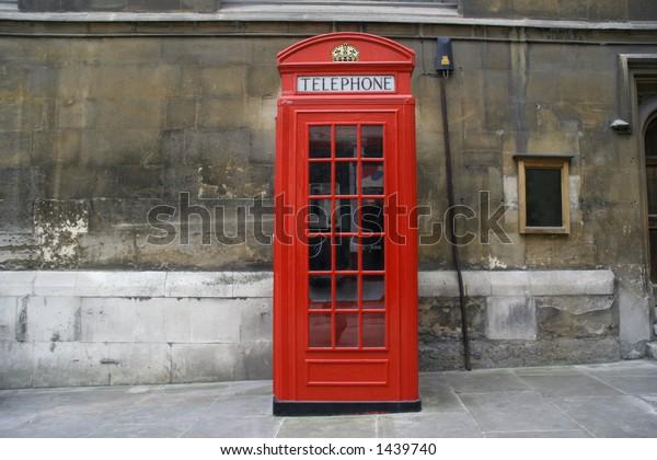 traditional london phone box on a slanted street