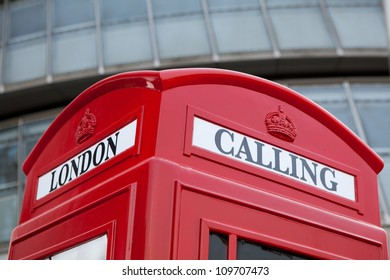 Traditional London symbol red public phone box for calling on the modern business center facade background