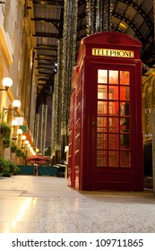 Traditional London symbol red public phone box in illuminated and festively decorated empty trade passage in evening. Great Britain
