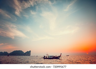 Traditional long boat and beautiful tropical sunset in Krabi, Thailand. Dramatic and picturesque evening scene. Ocean and colorful cloudy sky in the background. Nature landscape. Travel background