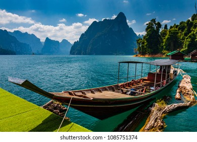 Traditional longtail boat on a beautiful lake surrounded by towering cliffs and lush jungle scenery