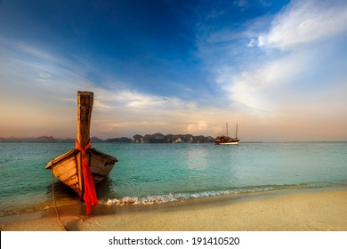 Traditional longtail boat at sunset on tropical island, Thailand