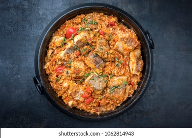 Traditional Louisiana fish jambalaya dish creole cajun with rice and tomatoes as top view in a pot with copy space
