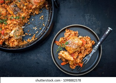 Traditional Louisiana fish jambalaya dish creole cajun with rice and tomatoes as top view in a pot and on a plate