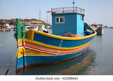 A traditional Luzzu fishing boat moored in the harbour of Marsaxlokk in Malta.