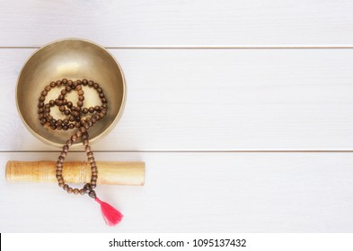Traditional mala beads and tibetan singing bowl on white wooden background with copy space. Essential accessory for mindfulness or meditation.