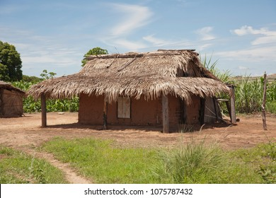 Traditional malagasy house with thatched roof. Village in Madagascar, blue sky, green grass.