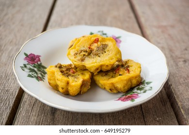 """Traditional Malay Kuih (kueh) called """"Cara Berlauk"""" in white flower plate over wooden background."""