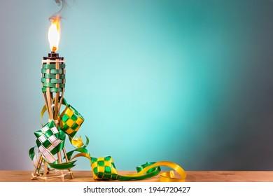 Torche traditionnelle malaise et ketupat décoratif allumé lors de la fête de Hari Raya Aidilfitri