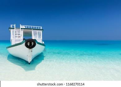 Traditional maldivian boat on pristine white sand beach on a sunny day