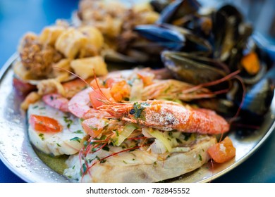 Traditional maltese fish and seafood platter set mix of calamari rings in tempura, giant shrimps, clams, fish fillets and mussels served in local restaurant. Delicious maltese cuisine