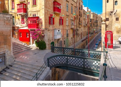 The traditional Maltese street with red phone box, shutters and balconies in Valletta, Capital city of Malta