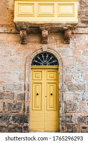 A traditional Maltese wooden door, painted yellow, and stone facade of a traditional old Maltese house.