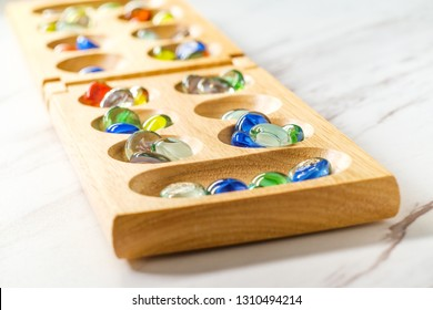 Traditional Mancala boardgame with glass pieces on marble table