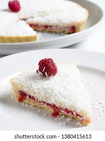 Traditional Manchester Tart on white marble with raspberries and coconut