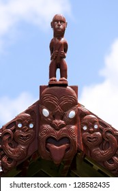 Traditional Maori wood carving on top of a Whare Waka (Canoe house) in New Zealand.