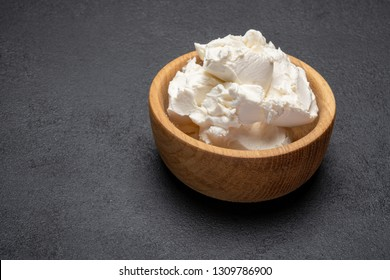 Traditional Mascarpone cheese in wooden bowl on concrete background