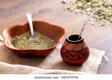 Traditional mate made of calabash over a wooden table with yerba mate scattered over it.