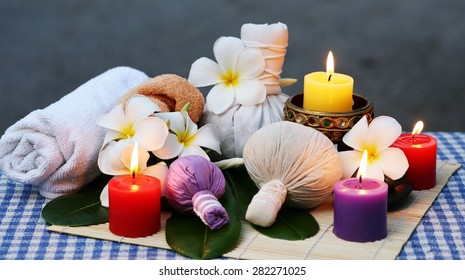 Traditional Medicine of Thailand, Herbal Ball for massage and spa decorated with frangipani and lighting candles at night