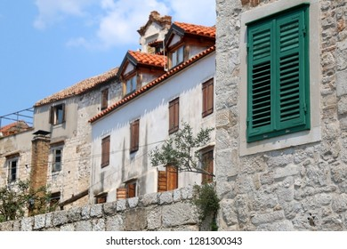 Traditional Mediterranean architecture in Sibenik, Croatia. Stone walls and woode windows with olive plant in the garden. Sibenik is popular summe travel destination.